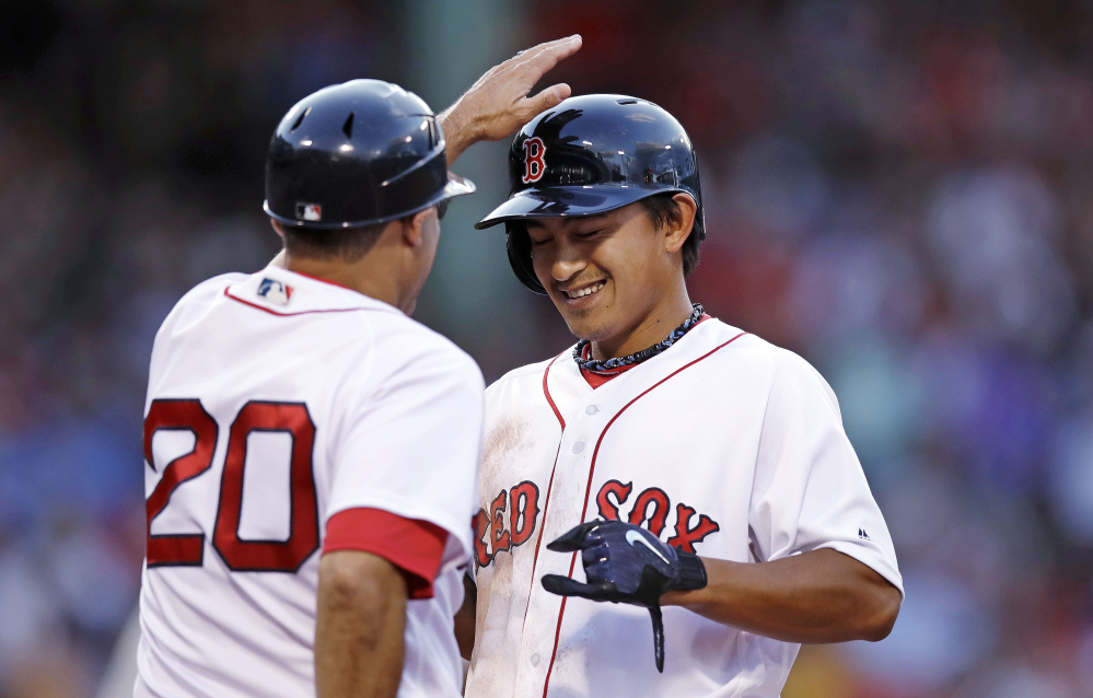 Red Sox rookie Tzu-Wei Lin gets a congratulatory tap on the helmet by first base coach Ruben Amaro Jr. after his first major league hit, a single in the second inning.