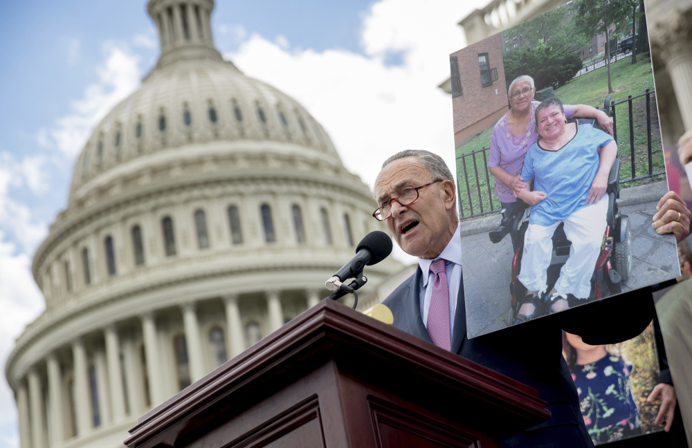 Senate Minority Leader Sen. Chuck Schumer of New York holds up a photograph of constituents who would be adversely affected by the proposed Republican Senate health care bill as he and Democratic senators speak outside the Capitol Building in Washington on Tuesday.