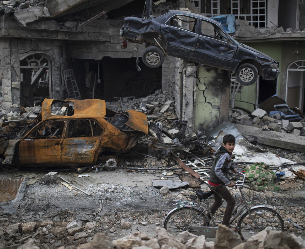 A boy rides his bike past destroyed cars and houses in a neighborhood liberated by Iraqi security forces in March, on the western side of Mosul, Iraq.