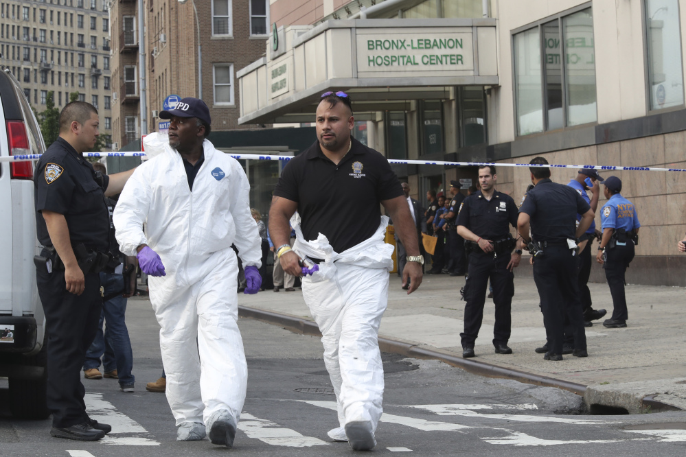 Police officers with the Forensics Unit leave Bronx Lebanon Hospital after a doctor who used to work there opened fire with an AR-15 and then took his own life there on Friday in New York.