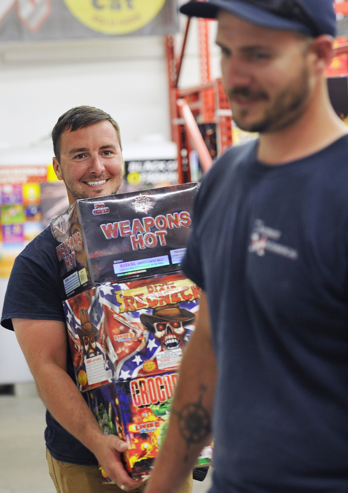 Ben Wittman of Windham, left, leaves Pyro City Fireworks in Windham with an armful of fireworks on Friday.