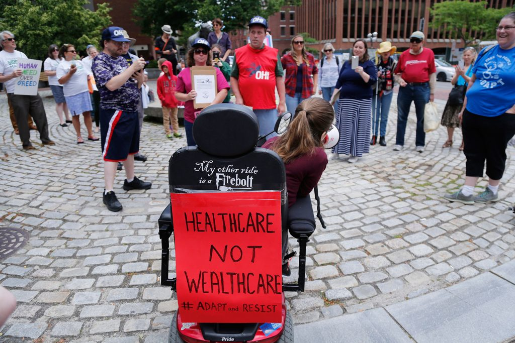 Kingsley Floyd, a Waynflete School graduate who was arrested at a protest in front of Senate Majority Leader Mitch McConnell's office last week, speaks a rally for health care Wednesday at Lobsterman's Park in Portland. She said people with disabilities need Medicaid funding to be able to live independently.