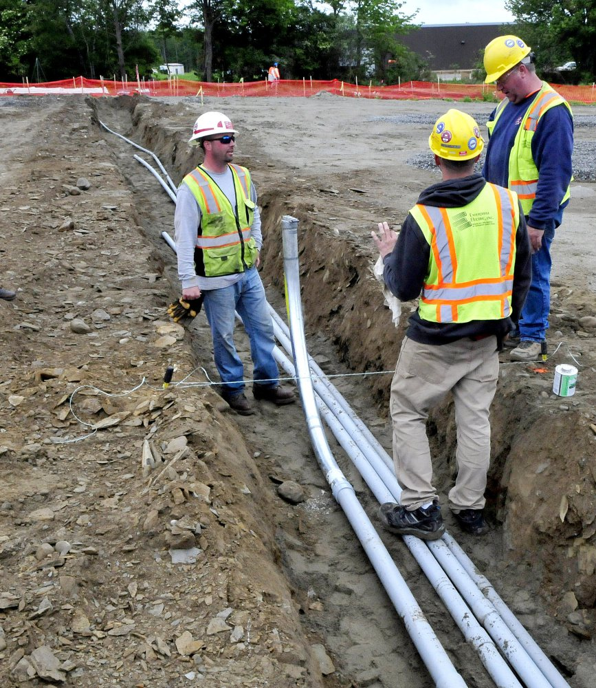 Subcontractors lay conduit to carry electricity from the new solar array under construction near Colby College in Waterville to campus on Monday.