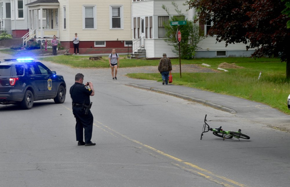 A Waterville police officer takes photos of the scene where a child struck a car while riding his bicycle Tuesday on Western Avenue in Waterville.