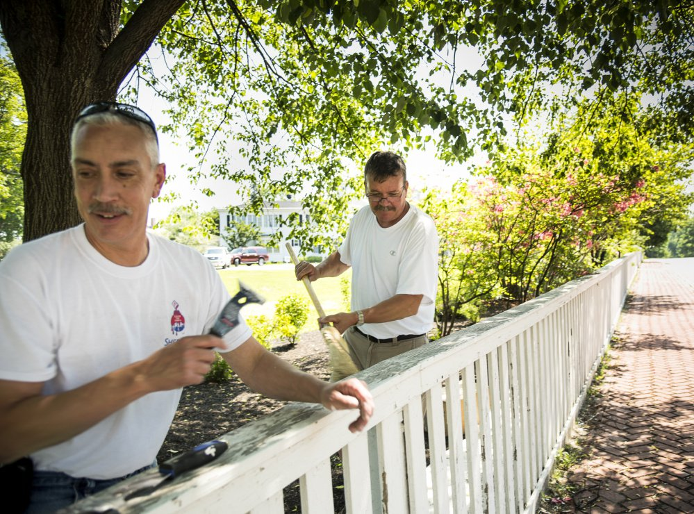 Painters Jeff Gregoire, left, of Augusta and Ted Brown, of West Gardiner, work in the shade as they scrape and paint the fence at the Blaine House in Augusta on Monday. Temperatures were expected to reach into the 90s, prompting Augusta elementary schools to let students go home early.