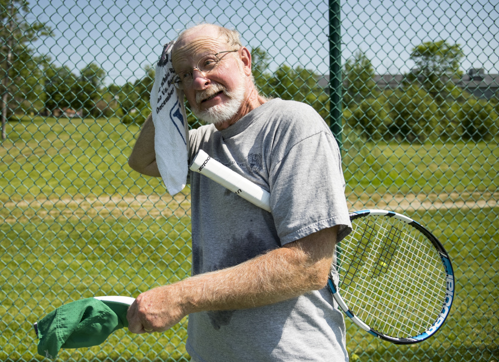 Doug Legg, of Waterville, pauses to towel off sweat during a doubles tennis match with friends at the tennis courts on Capitol Street in Augusta on Monday.