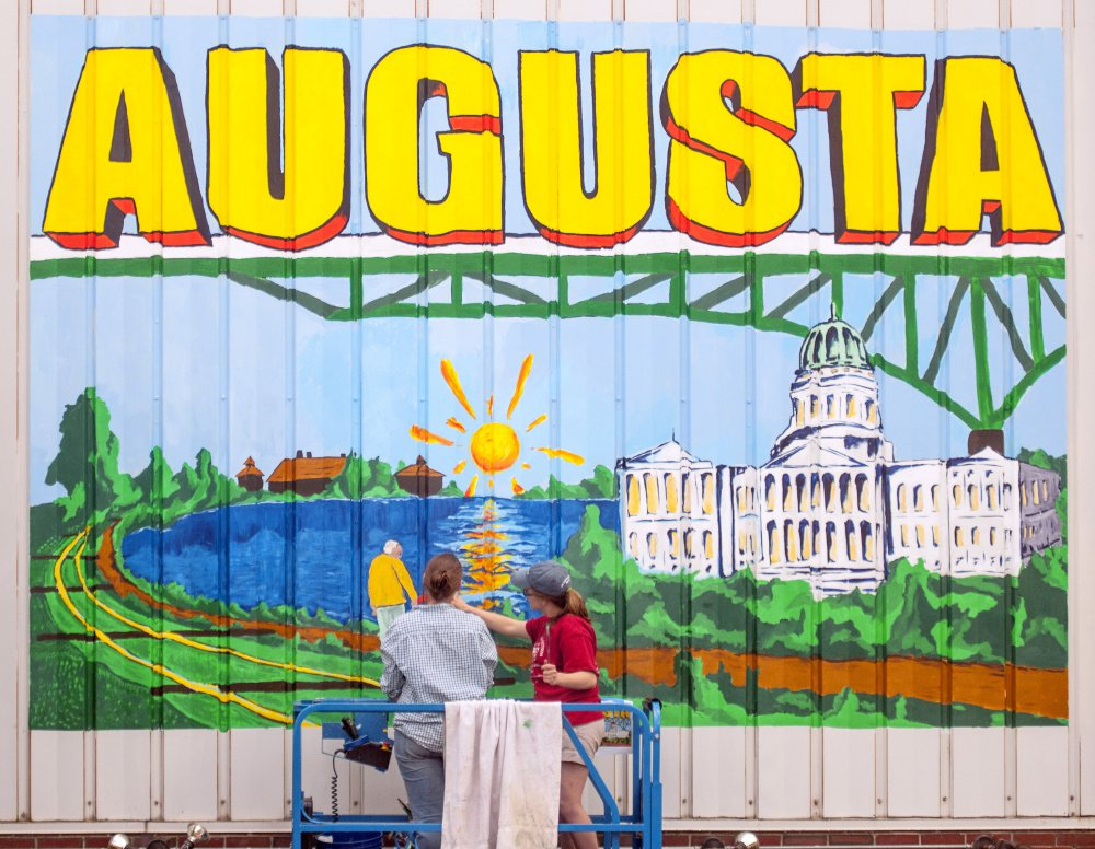Staff photo by Joe Phelan University of Maine at Augusta art students Marcea Crawford, left, and Sierra Meservey work on June 15 in a scissor lift on a large postcard-style mural on the side of 179 Water St. overlooking the intersection of Bridge and Water streets in downtown Augusta. It was the first downtown mural to be completed, with others in the works.
