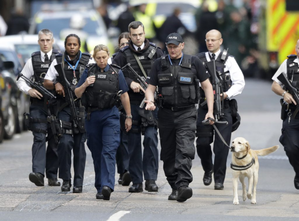 British police officers walk with a detection dog within a cordoned-off area after the attack in London on Sunday.