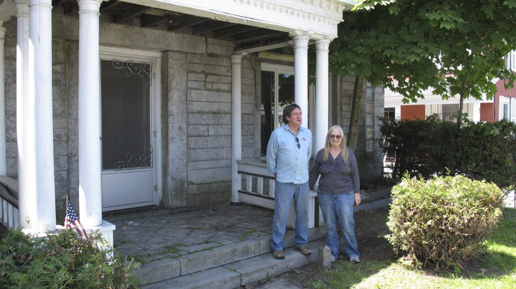 Brian and Joan DuMoulin pose on both sides of a marker showing the U.S.-Canadian border in the front yard of their home. She is in Canada, while he is in the United States. The fact that the house straddle the border between Beebe Plain, Vt., and Stanstead, Quebec, has made it more difficult to sell.