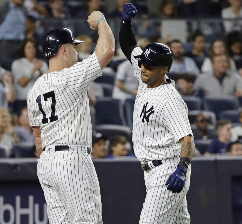 Matt Holliday, left, celebrates with Aaron Hicks after Hicks hit a home run during the sixth inning Friday night in New York.