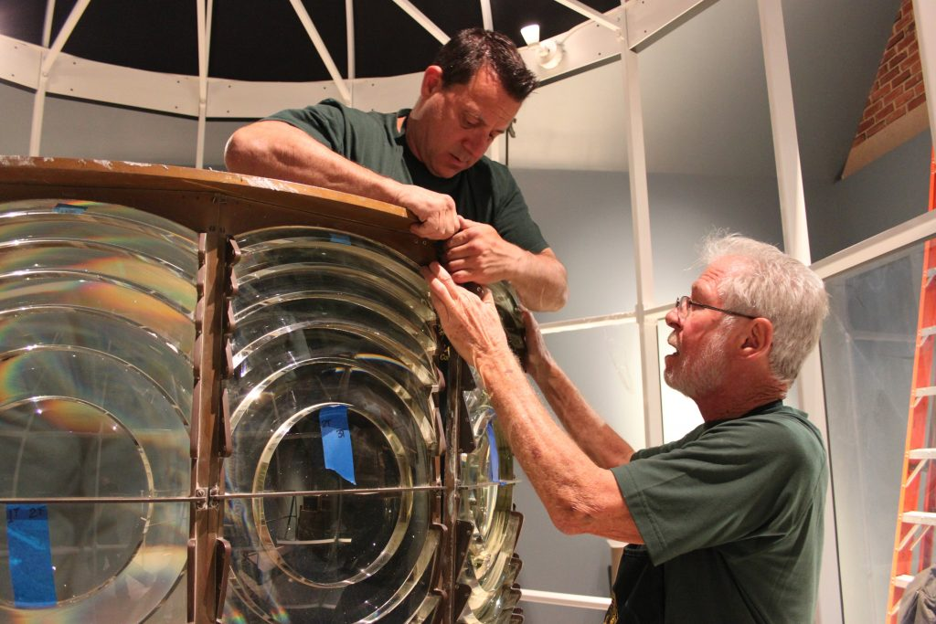 Tommy Cumella works inside Cape Elizabeth Two Light's second-order Fresnel lens as Jim Dunlap makes sure there's no risk of the lens falling.