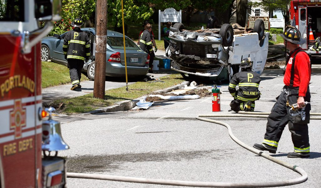 Firefighters clear the scene of a two-vehicle collision in the North Deering neighborhood of Portland on Thursday. Several blocks of Auburn Street were closed near Northgate Plaza.