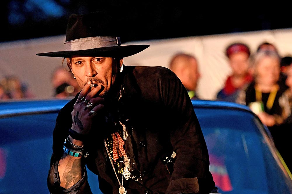 "Johnny Depp poses on a Cadillac before presenting his film ""The Libertine,"" at Cinemageddon during the Glastonbury Festival in Britain, on Thursday."