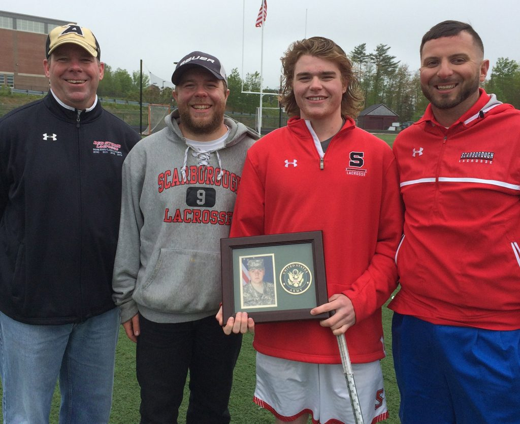 Sam Neugebauer, second from right, has been the leading scorer on the Scarborough boys' lacrosse team for the past two years. He completes a line of three Neugebauer brothers who have been in the program for 11 straight seasons. After the team's final regular season game, he posed with, from left, his father, Kyle, oldest brother Nick and Coach Joe Hezlep while holding a picture of middle brother Ben Neugebauer, who is stationed in Texas in the Army.