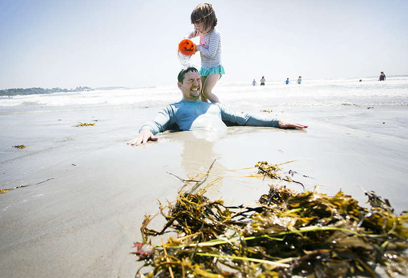 Lucy Mosher, 3, of Schenectady, NY, dumps a bucket of water on her father, Brian, after burying him in the sand during their family vacation at Higgins Beach in 2016.