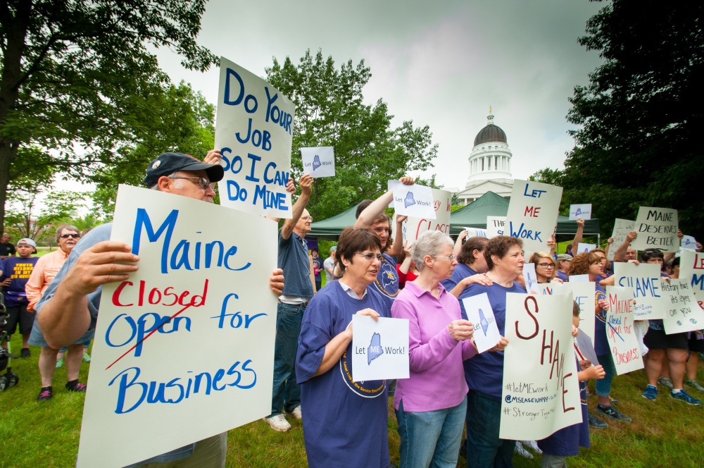 Protesters hold signs Saturday morning in Capitol Park in Augusta, in front the the State House, objecting to the state government shutdown that resulted from lawmakers' failure Friday to pass a budget that was veto-proof or acceptable to Gov. Paul LePage.