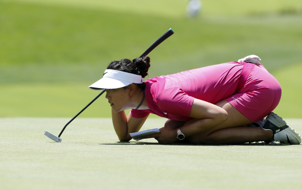 Michelle Wie reads the fifth green – as well as her notes – while lining up her putt during the third round of the KPMG Women's PGA Championship on Saturday afternoon. Wie is tied for seventh at 5 under, four shots off the lead.