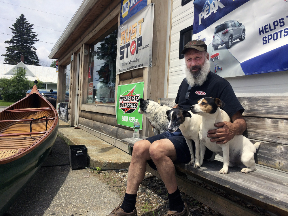 Domenic Pono sits with his three Jack Russell terriers outside his store, Dom's Auto and Jeep Repair, on Main Street in Rangeley. He's hopeful the prospective new owners of Saddleback ski area, the Majella Group, will keep the character of the mountain if it's expanded to a four-season resort.