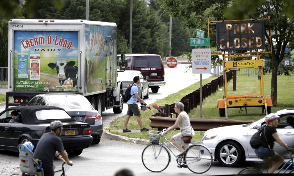 Vehicles, cyclists and walkers bottleneck Saturday at the entrance to Liberty State Park in Jersey City, where a roadblock is keeping them from the park, which remains closed because of the New Jersey government shutdown.