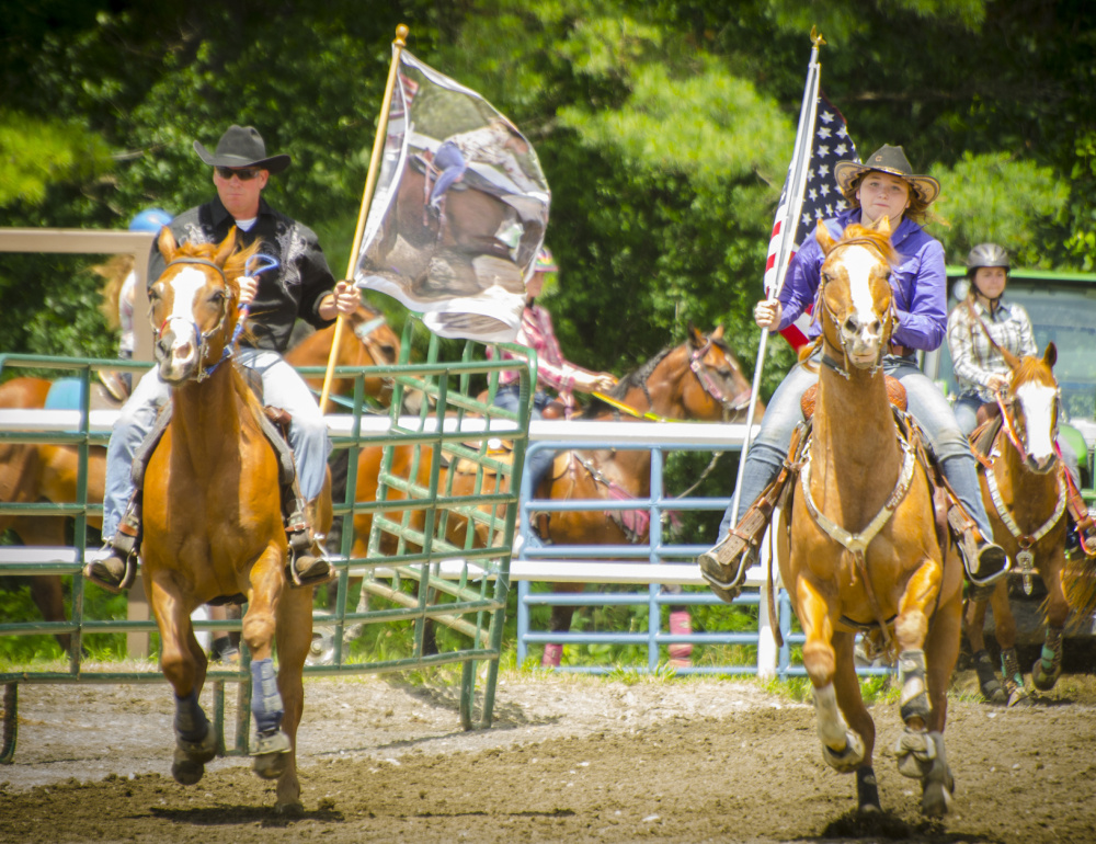 Hardy Cummings, left, and Harmony Renaud lead the start of the Halee Lyn Cummings Memorial Barrel Race. Cummings started the event to honor his late daughter.