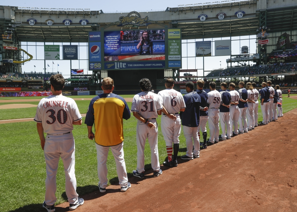 Milwaukee Brewers players line up for the national anthem before Monday's game against the Baltimore Orioles, in a baseball tradition that's in its 100th season.