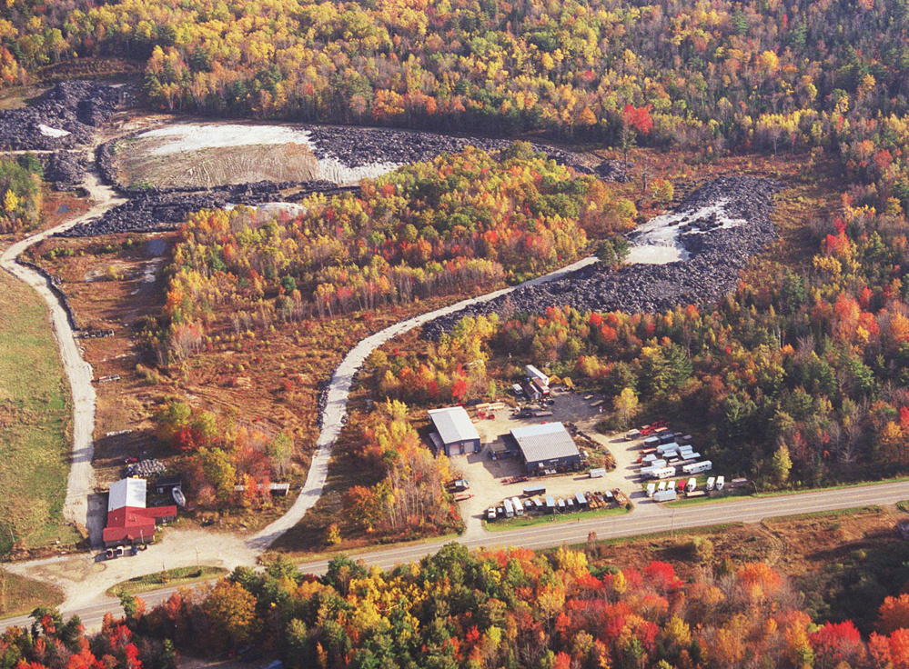 A 2001 aerial photo shows fiber material waste in Warren, with Route 90 in the foreground. Only 1,000 of the 27,000 tons of waste have been removed under a contract that expired in April, and