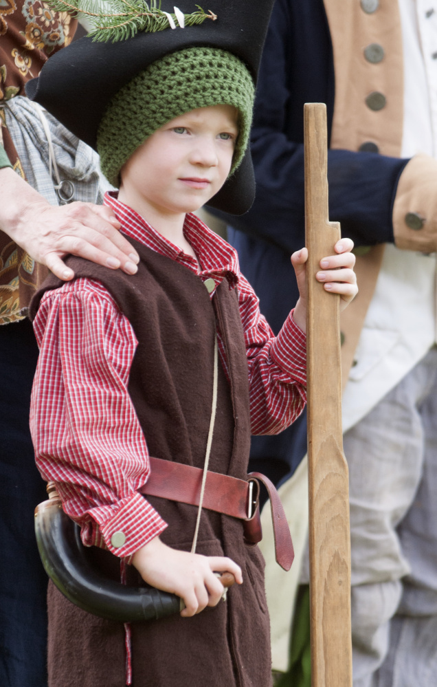 Re-enactor Benjamin Bickford, 4, of Oakland, stands with his mother, Eileen Bickford, and other re-enactors during a ceremony Tuesday at Old Fort Western in Augusta.