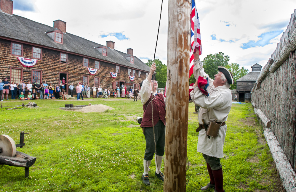 Re-enactors Jackie Fournier, left, and Stan Novak take down a Grand Union flag and swap it for one with thirteen stars and stripes Tuesday at Old Fort Western in Augusta.
