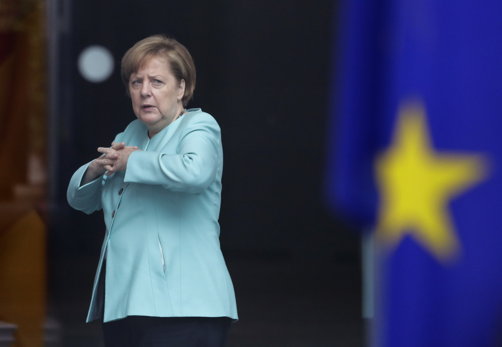 German Chancellor Angela Merkel stands behind a European flag as she waits for the arrival of Chinese President Xi Jinping at the chancellery in Berlin on Wednesday.