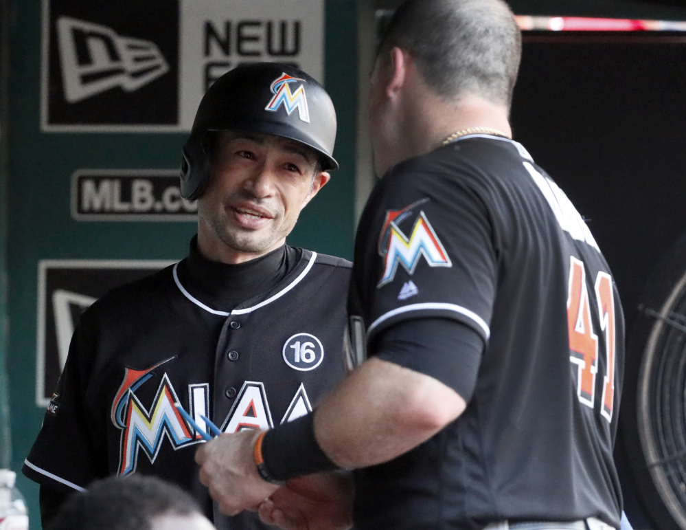 Ichiro Suzuki, left, of the Miami Marlins talks with teammate Justin Bour after becoming the career hits leader for foreign-born players during a 4-3 loss to the St. Louis Cardinals.
