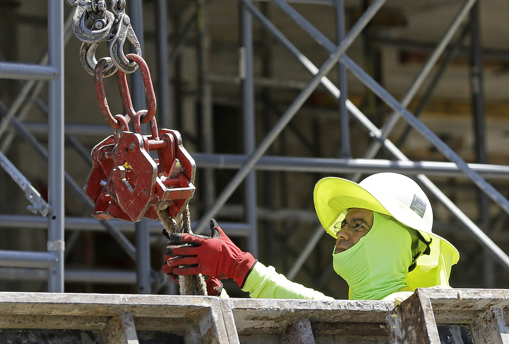 A construction worker works on a condominium project in Coral Gables, Fla. The Labor Department report for June shows the most jobs growth in four months.