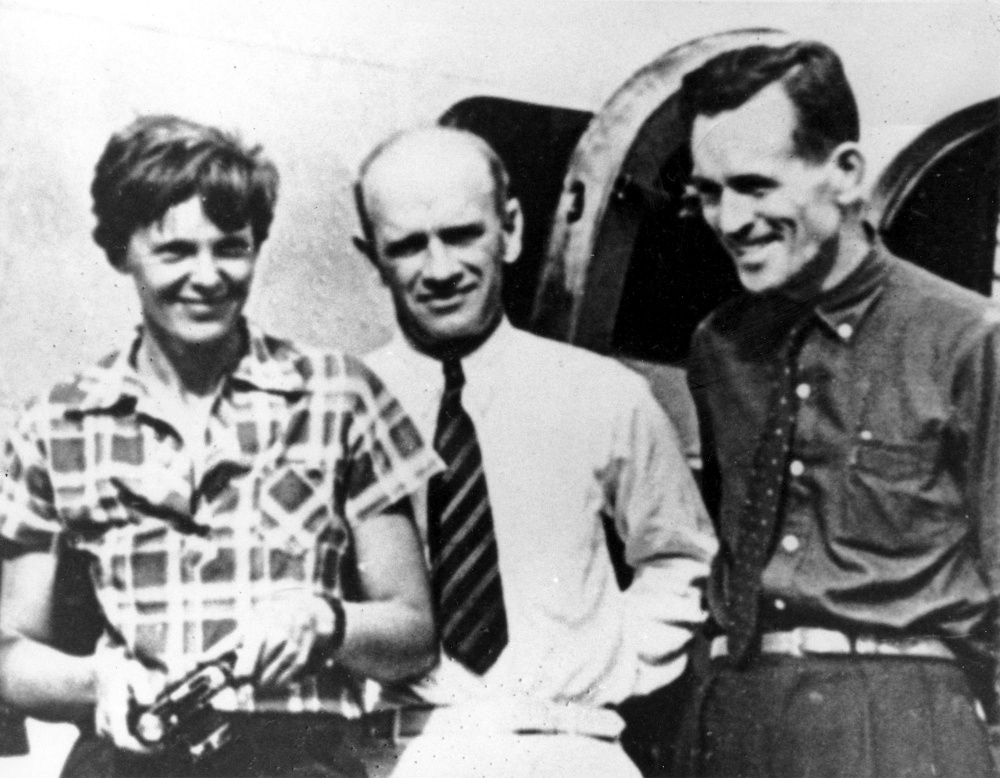 Amelia Earhart, left, and her navigator, Fred Noonan, right, pose beside their plane with gold miner F.C. Jacobs at Lae, New Guinea just before Earhart and Noonan took off on their final fateful flight.