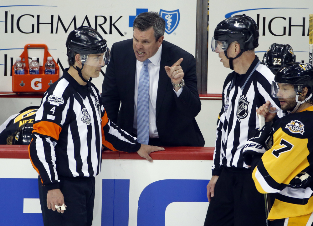 Wes McCauley of South Portland, left, listening to Pittsburgh Penguins Coach Mike Sullivan, was one of the four referees selected to work the Stanley Cup finals this year. Highly respected, he's been involved in the past five finals.