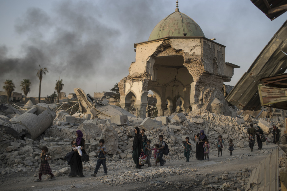 Fleeing Iraqi civilians pass a damaged mosque in Mosul earlier this week. After years of training by a U.S.-led coalition, Iraqi security troops still struggle to hold liberated territory.