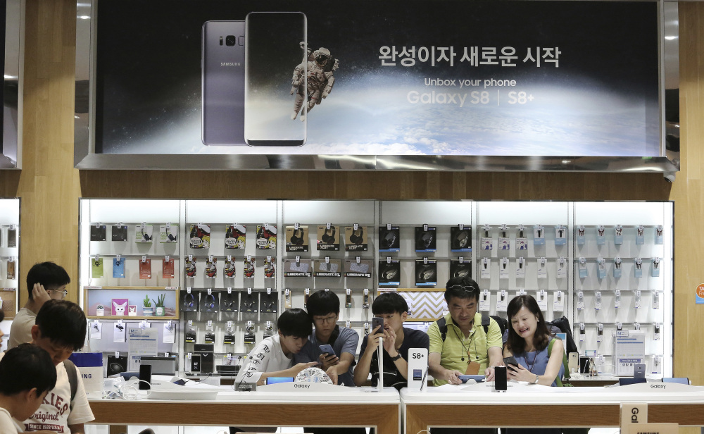 Visitors experience the Samsung Electronics Galaxy S8 Plus smartphone at one of the company's stores in Seoul, South Korea. The tech company said Friday its second-quarter operating profit soared to the highest in its history.