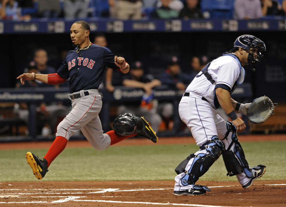 Boston's Mookie Betts scores past Tampa Bay catcher Wilson Ramos on Andrew Benintendi's RBI single during the third inning Friday in St. Petersburg, Fla.