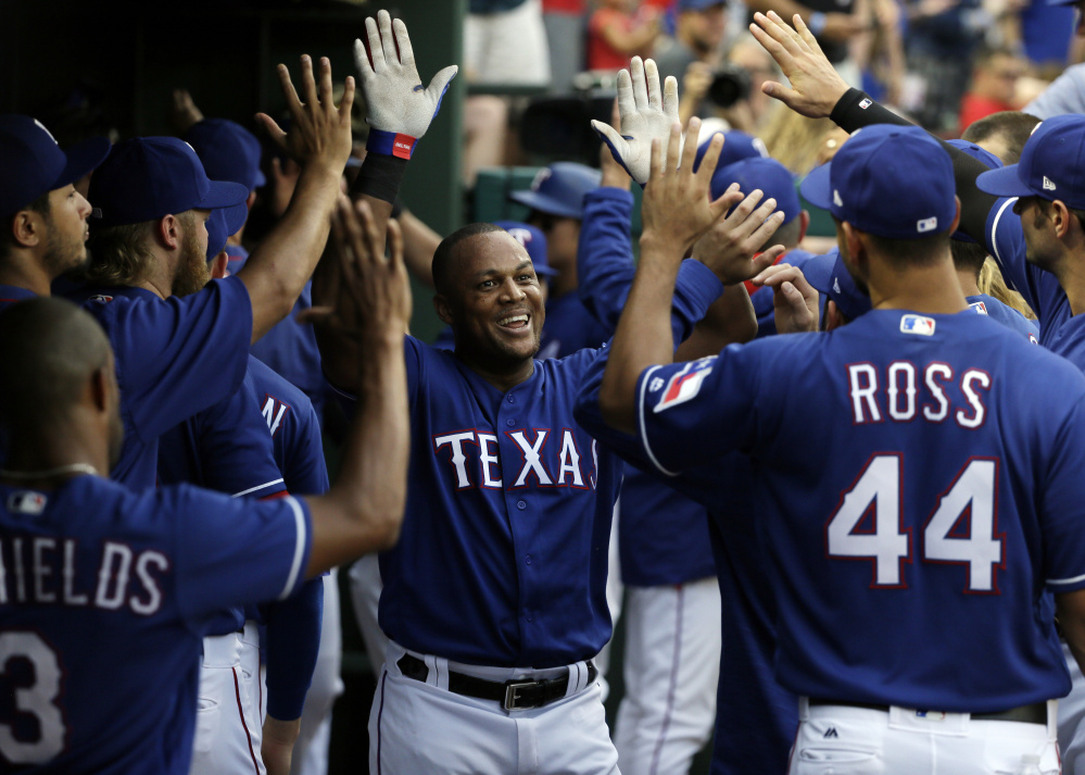 Texas Rangers' Adrian Beltre, center, is congratulated in the dugout after hitting a three-run home run off Los Angeles Angels starting pitcher Ricky Nolasco in the second inning Friday in Arlington, Texas. The hit was Beltre's 2977th career hit.
