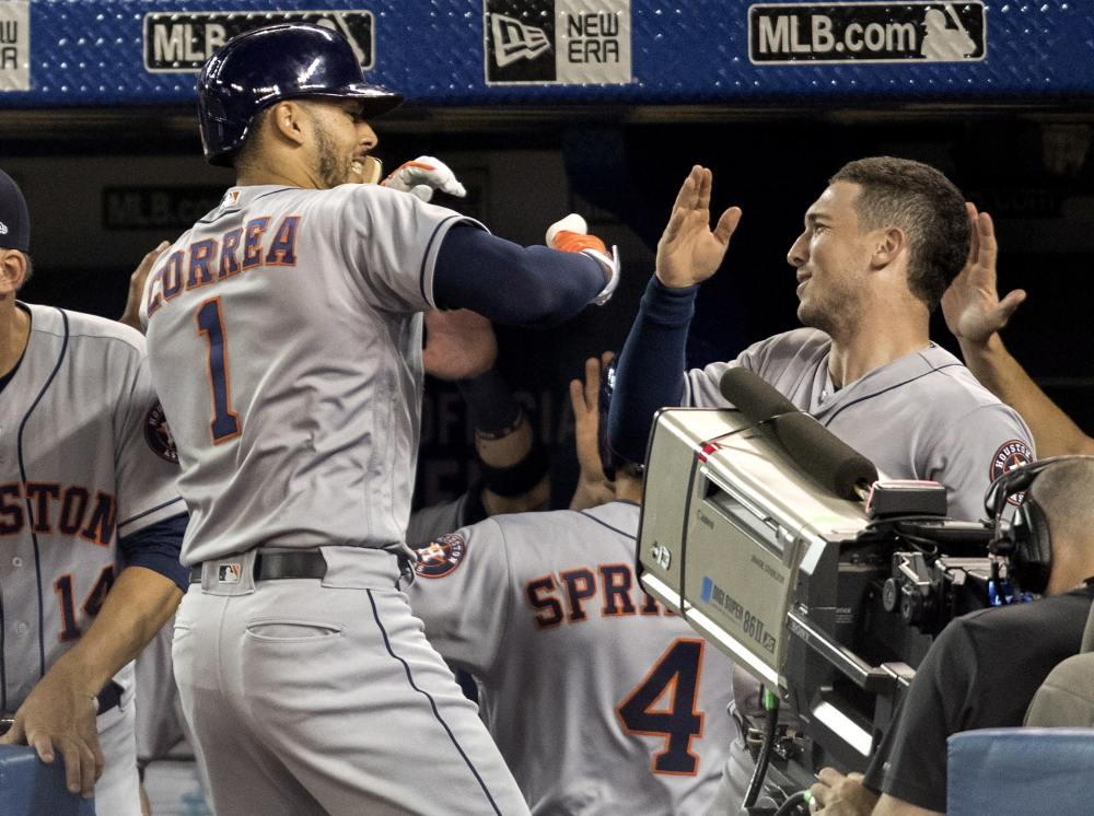Carlos Correa of the Houston Astros is greeted by teammates Friday night after hitting a two-run homer in the first inning of a 12-2 victory against the Toronto Blue Jays.