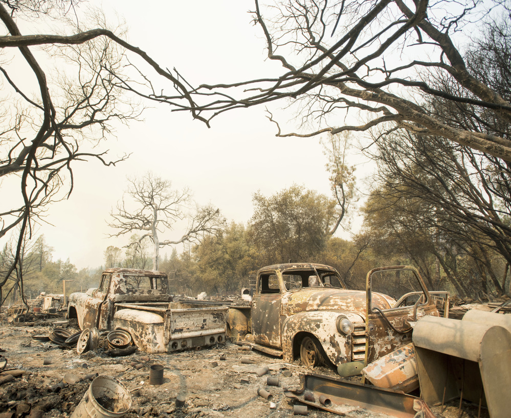 A wildfire left vintage trucks burned near Oroville, Calif., on Saturday. The fire south of Oroville was one of more than a dozen burning around the state in scorching temperatures.