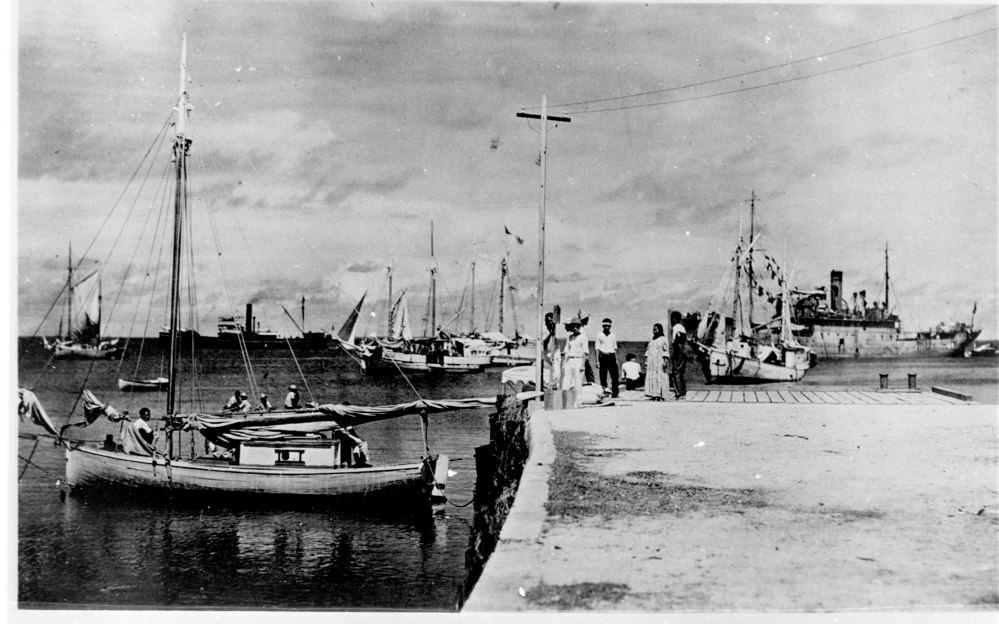 "This photo discovered in the National Archives shows people on a dock in Jaluit Atoll, Marshall Islands. A new documentary proposes that the image shows aviator Amelia Earhart, seated third from right, gazing at what may be her crippled aircraft loaded on a barge. The documentary, ""Amelia Earhart: The Lost Evidence,"" aired Sunday on the History Channel."