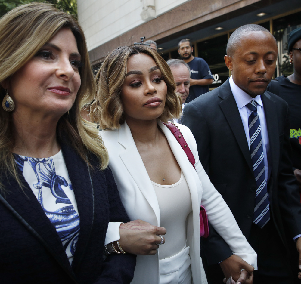 Blac Chyna, center, is flanked by her attorneys, Lisa Bloom, left, and Walter Mosley as she leaves court after a hearing Monday.