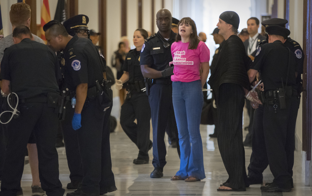 Activists protesting the Republican health care bill Monday are taken into custody by U.S. Capitol Police outside Senate offices on Capitol Hill.