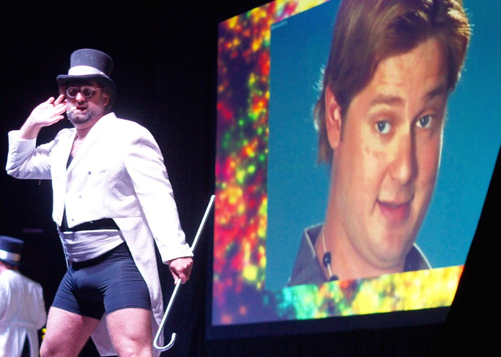 Eric Wareheim is standing and Tim Heidecker is on the screen