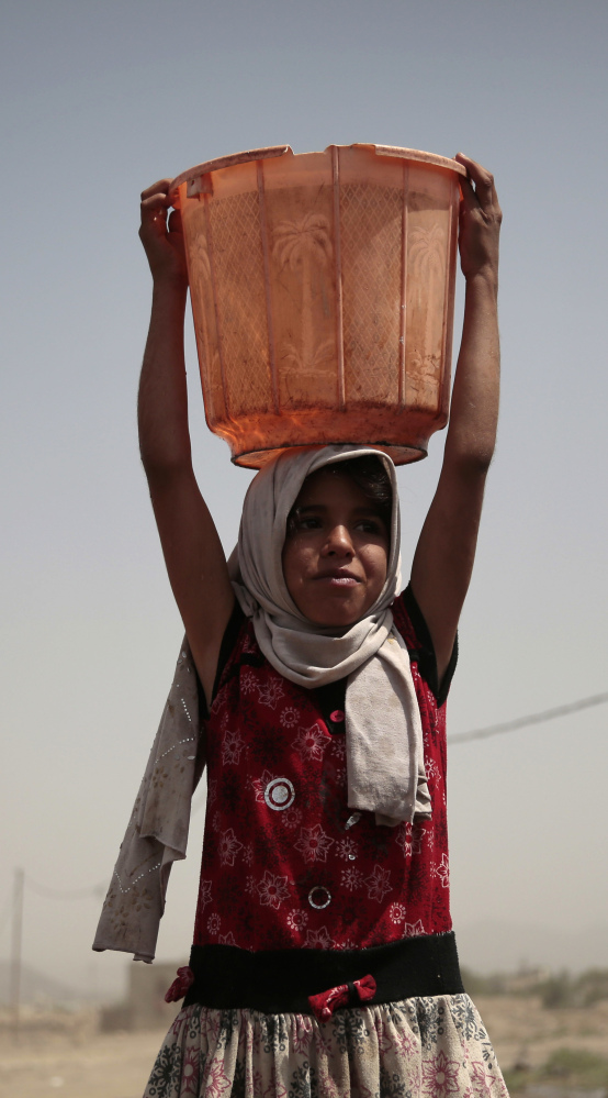 A girl carries a bucket filled with water from a well that is allegedly contaminated with cholera in Yemen.