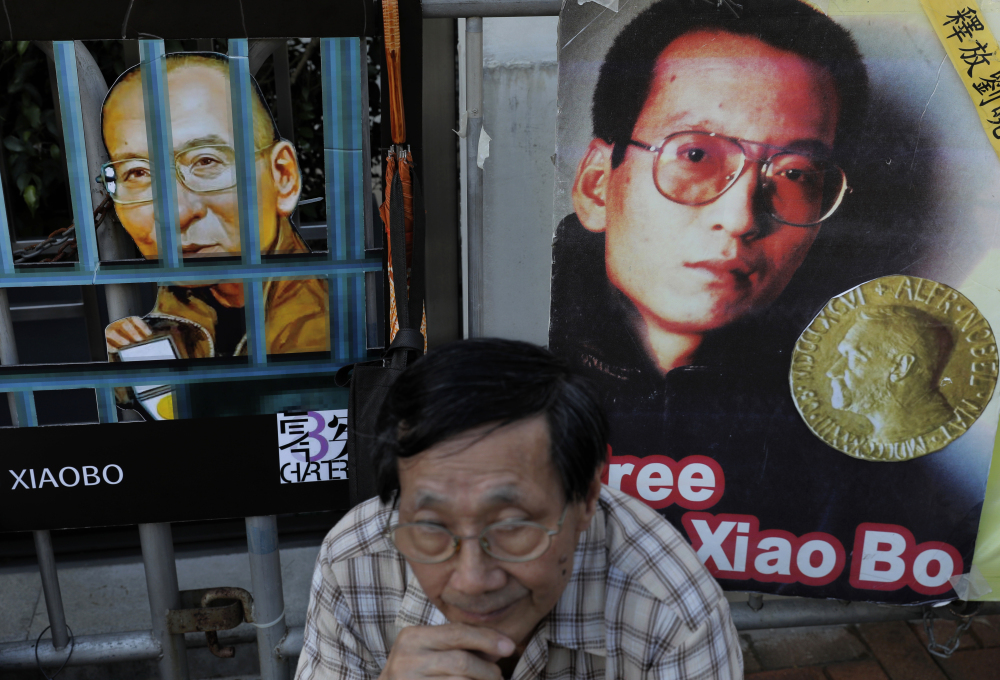 A protester sits in front of pictures of jailed Chinese Nobel Peace laureate Liu Xiaobo during a demonstration outside the Chinese liaison office in Hong Kong on Thursday.