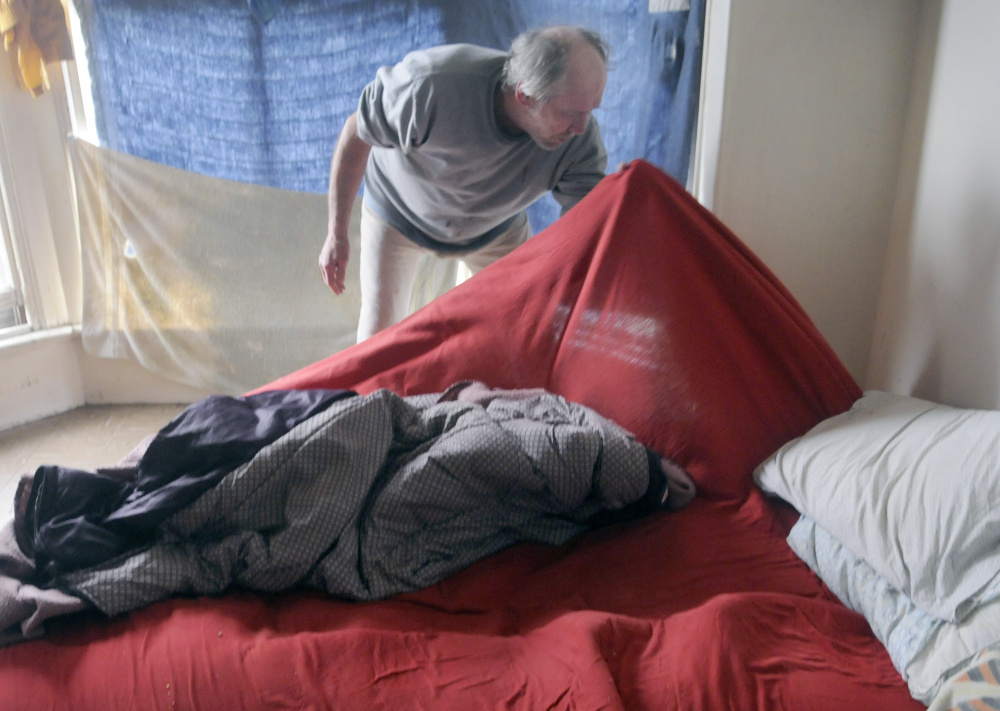 Al Sugden of Augusta searches his bedding for bedbugs in his Water Street apartment in May 2016. To help solve the city's bedbug problem, an anonymous donor has offered to put up $20,000 if others will match it.