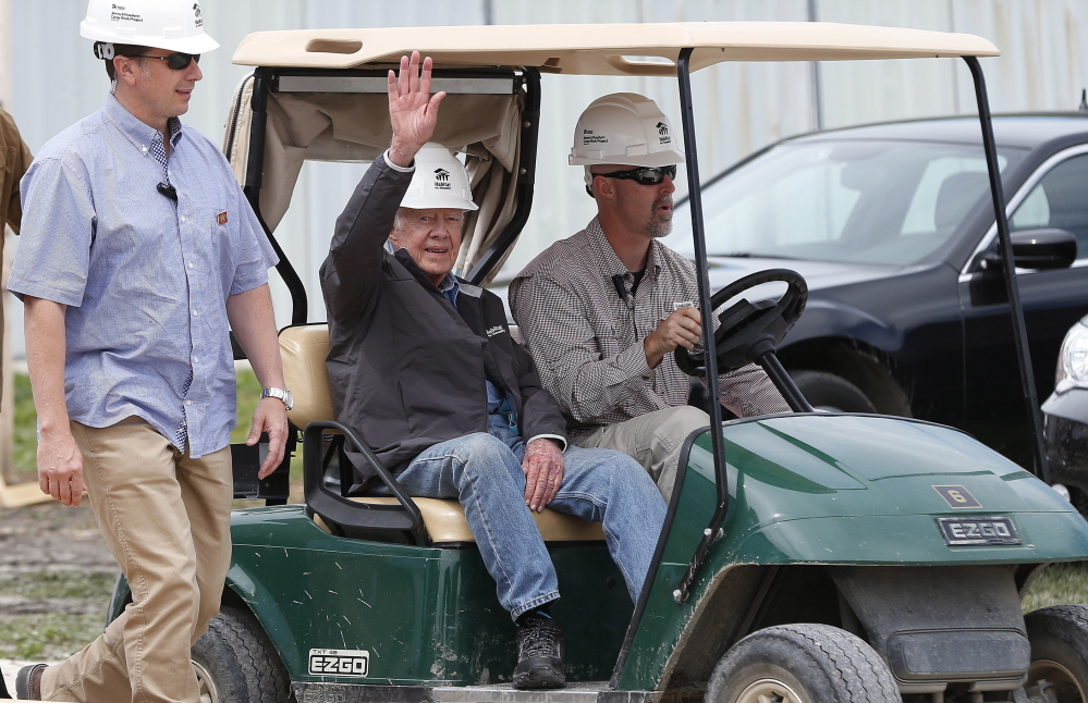 Former President Jimmy Carter waves to assembled crowd members as he returns to a Habitat for Humanity site Friday.