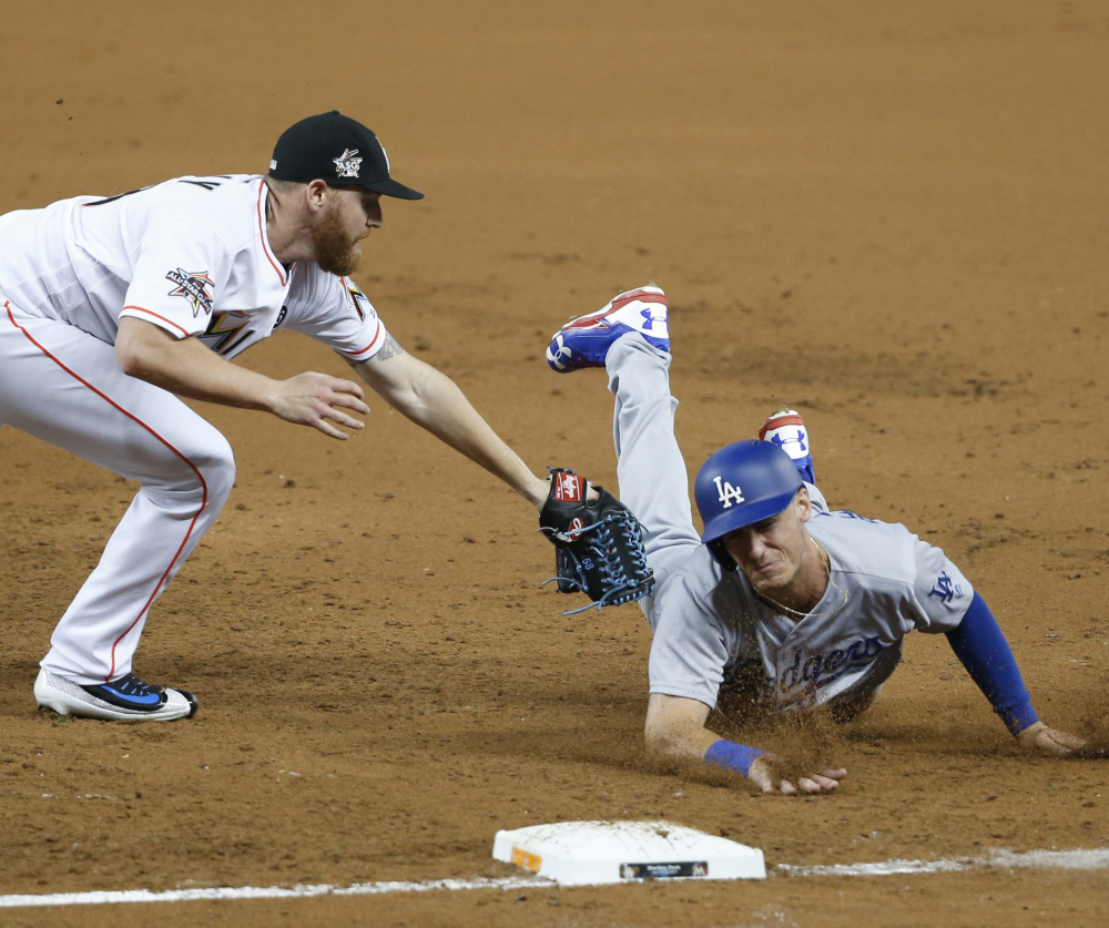 Miami pitcher Dan Straily tags out Cody Bellinger of the Los Angeles Dodgers, who was caught between first and second base in the third inning Friday night. The Dodgers won, 6-4.
