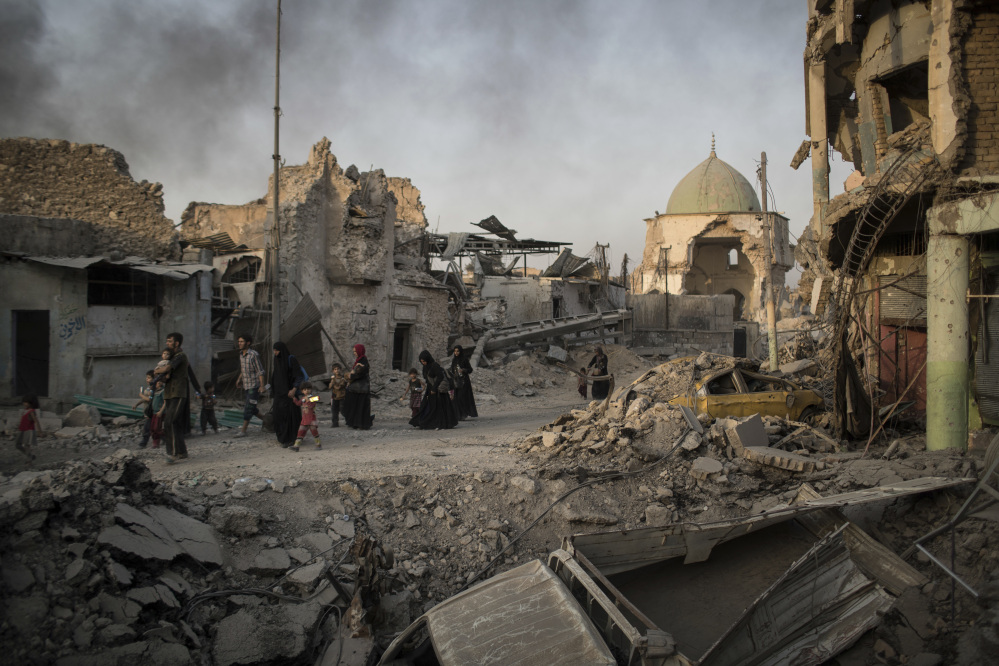 Fleeing Iraqi civilians walk past the heavily damaged al-Nuri mosque during fights between Iraqi security forces and Islamic State militants in the Old City of Mosul, Iraq, in early July.
