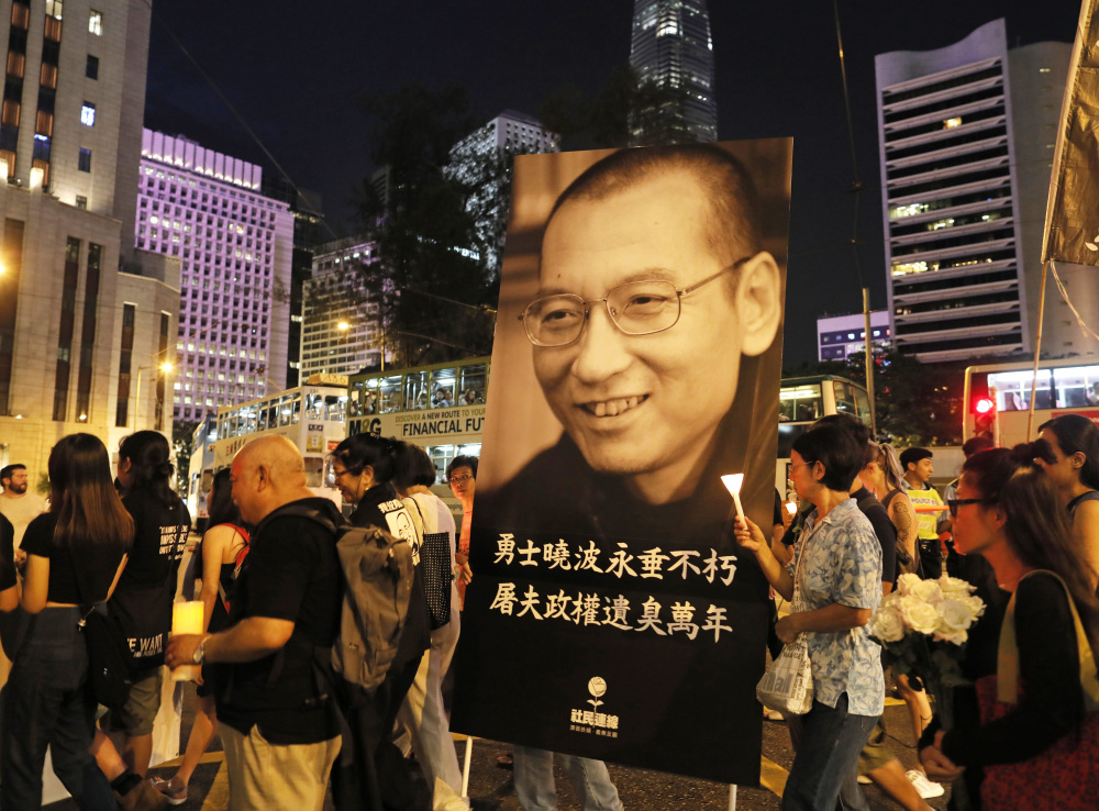 Protesters carry a picture of the late Chinese Nobel Peace laureate Liu Xiaobo as they march to mourn him in Hong Kong, on Saturday. Associated Press/Vincent Yu